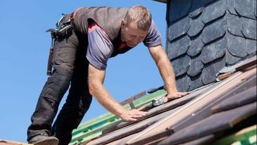 A roofer retiling a roof