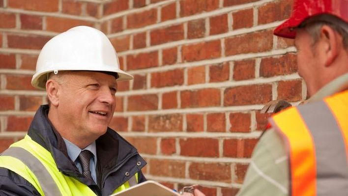 A roofer talking to a insurance agent