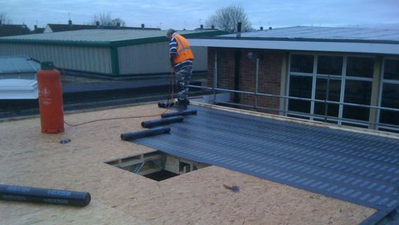 Roofing experts installing a flat roof